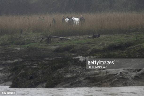 Police officers search the area on March 8 2017 in PontdeBuis western France after the brotherinlaw of a Frenchman who went missing with his wife and...