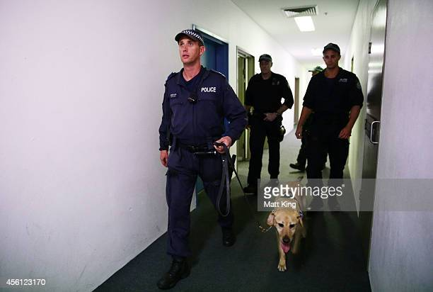 Police officers search the inner precinct of ANZ stadium using a sniffer dog during the First Preliminary Final match between the South Sydney...
