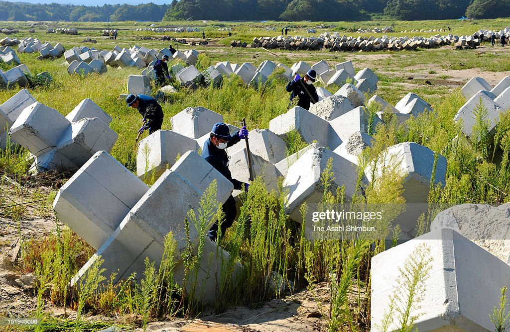 Police officers search the missings among the tsunami washed wave-dissipating blocks at former exclusion zone of the troubled Fukushima Daiichi Nuclear Power Plant on September 11, 2012 in Iwaki, Fukushima, Japan. 18 months on, still 2,814 people are missing and 340,000 people are forced to live at temporary housing.