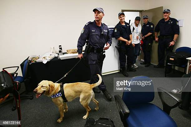 Police officers search the official photographers room using a sniffer dog during the First Preliminary Final match between the South Sydney...
