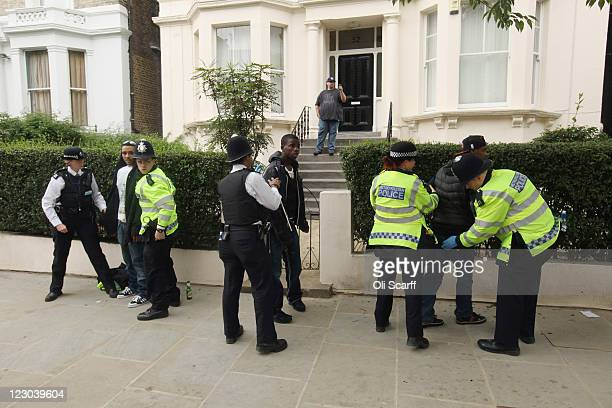 Police officers search young men one of whom is wearing a stab vest near to where a man was stabbed at the Notting Hill Carnival on August 29 2011 in...