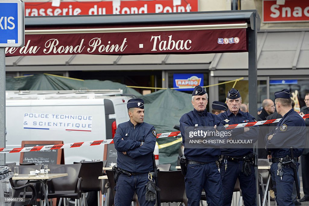 Police officers secure a crime scene on November 26, 2012 in Marseille, southeastern France, in front of a cigar store where a 47-year old man was shot dead by two unidentified people who stole his briefcase.