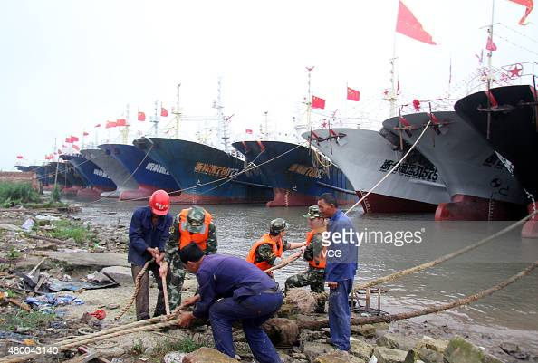 Police officers secure fishing vessels ahead of the arrival of Typhoon Linfa at a dock in Jinqing Town Luqiao District on July 9 2015 in Taizhou...