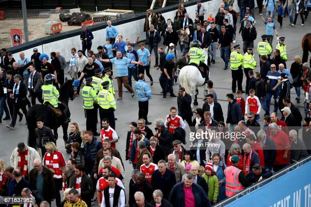 Police officers separate the fans prior to the Emirates FA Cup SemiFinal match between Arsenal and Manchester City at Wembley Stadium on April 23...
