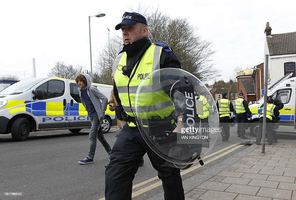 """Police officers set up a blockade on a street outside the ground before kick off in the English FA Cup fifth round football match between Luton Town and Millwall at Kenilworth Road Stadium, Luton, north of London on February 16, 2013. USE. No use with unauthorized audio, video, data, fixture lists, club/league logos or """"live"""" services. Online in-match use limited to 45 images, no video emulation. No use in betting, games or single club/league/player publications."""