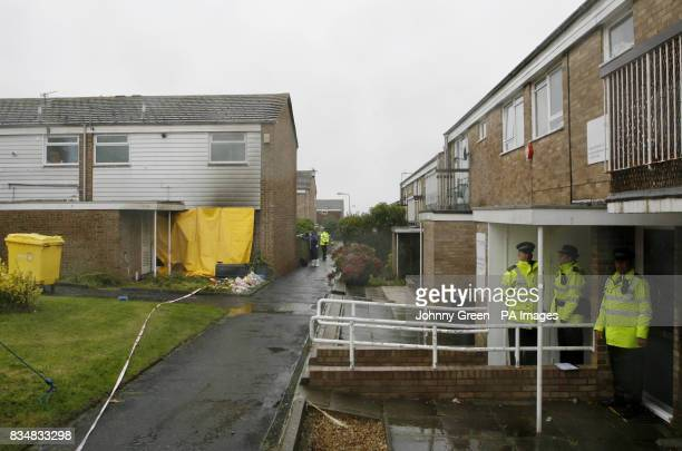 Police officers shelter from the rain as forensics officers conduct a full examination of a house in Milfoil Drive Eastbourne East Sussex where two...