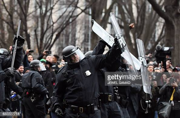 Police officers shield themselves as an antiTrump protester throw bricks during clashes in Washington DC on January 20 2017  Masked blackclad...