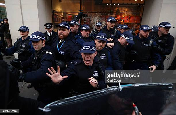 Police officers shout at protesters during a demonstration against fees and cuts in the education system on November 19 2014 in London England A...