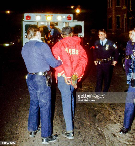Police officers smile at a handcuffed suspect arrested at the scene of a drugrelated shooting Washington DC 1994