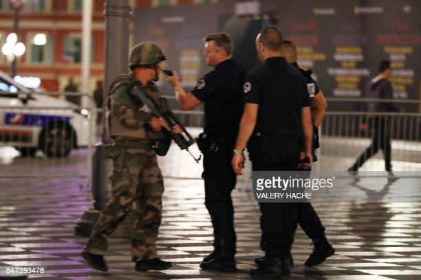 Police officers speak with a soldier after a truck that ploughed into a crowd leaving a fireworks display in the French Riviera town of Nice on July...