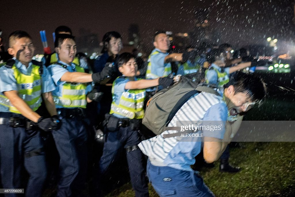 Police officers spray a prodemocracy protester in the face with pepper spray in Hong Kong on October 15 2014 Hong Kong has been plunged into the...