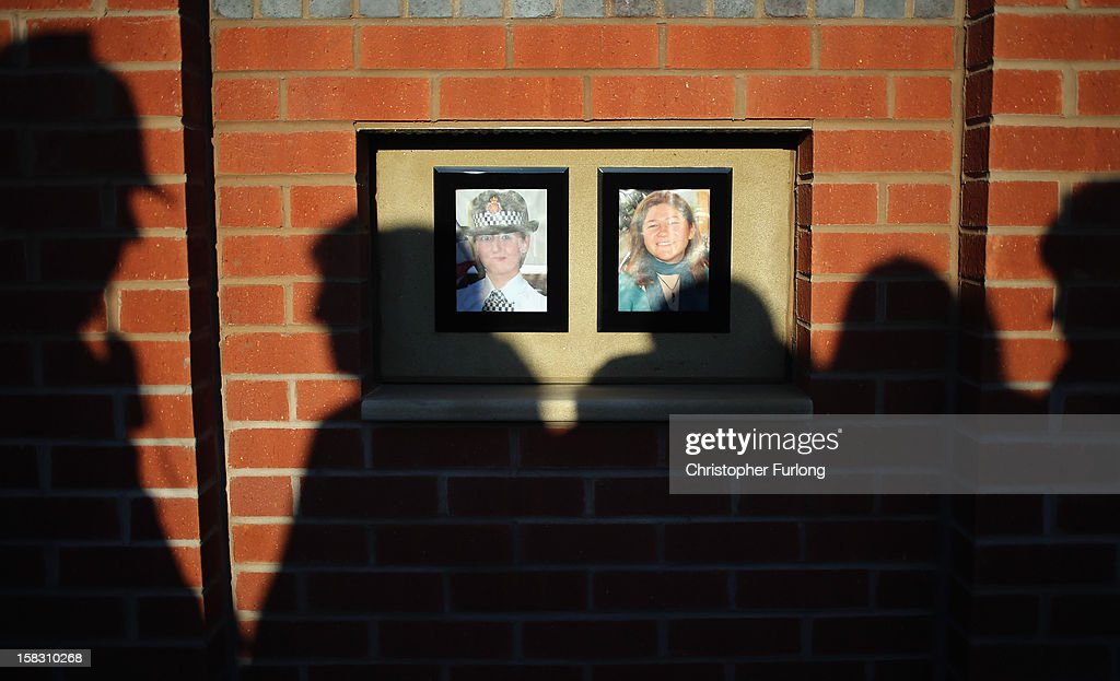 Police officers, staff and members of the public, pause for thought in the memorial garden dedicated to murdered PC's Fiona Bone and Nicola Hughes, which was unveiled today on December 13, 2012 in Hyde, England. Police Constables Fiona Bone, 32, and her colleague Nicola Hughes, 23, were killed as they responded to what they thought was a routine burglary call in Mottram, Greater Manchester and were murdered in a gun and grenade attack. The memorial garden outside Hyde police station has been created using funds donated by the public, businesses and police partners.