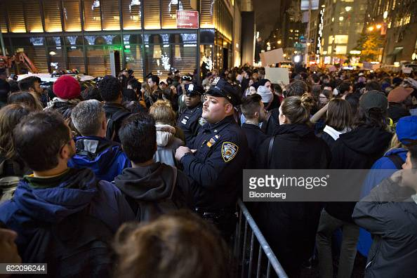 Police officers stand among demonstrators outside Trump Tower during a rally against US Presidentelect Donald Trump in New York US on Wednesday Nov 9...