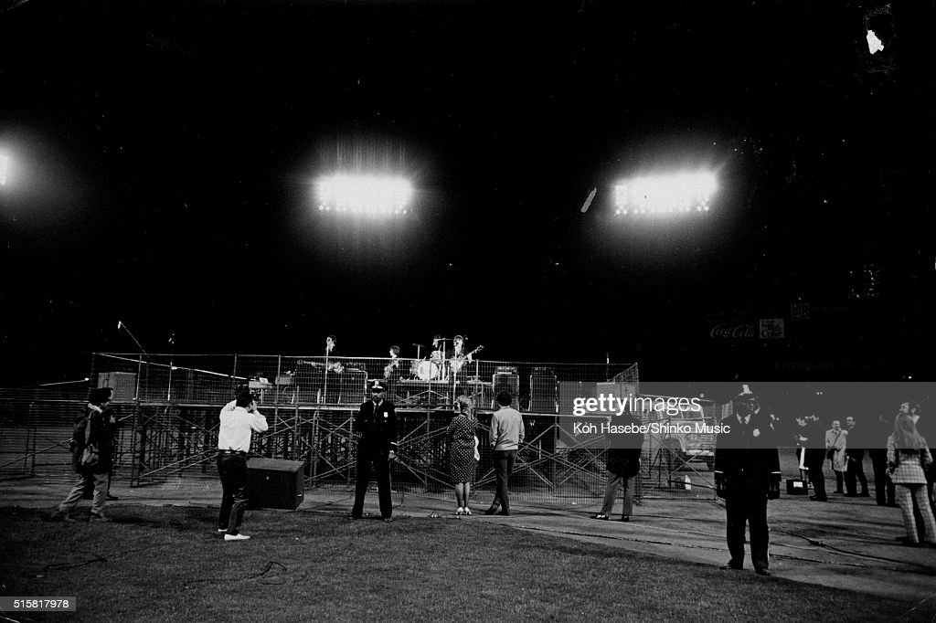 Police officers stand as security in front of the stage while The Beatles play the last show of their final tour at Candlestick Park San Francisco...