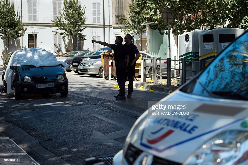 Police officers stand as they gesture by the car where two men in their twenties were shot dead near the train station SaintCharles in Marseille...