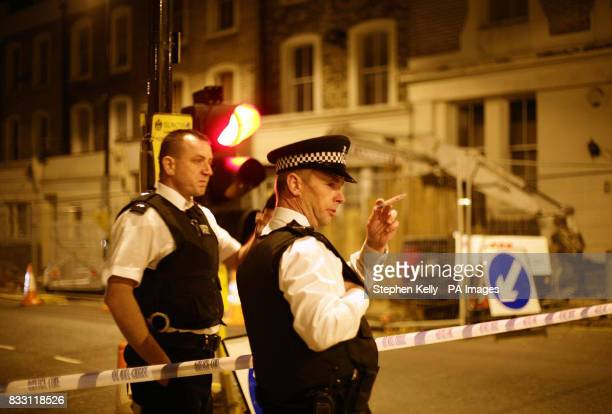 Police officers stand at a cordon in north London after a teenager was stabbed to death in the latest in a string of youth killings