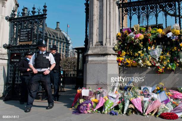 Police officers stand at the Carriage Gates entrance to the Houses of Parliament alongside floral tributes to the victims of the March 22 terror...