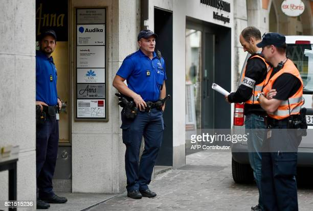 Police officers stand at the entrance of the building office in the old town of Schaffhausen northern Switzerland where a man armed with a chainsaw...