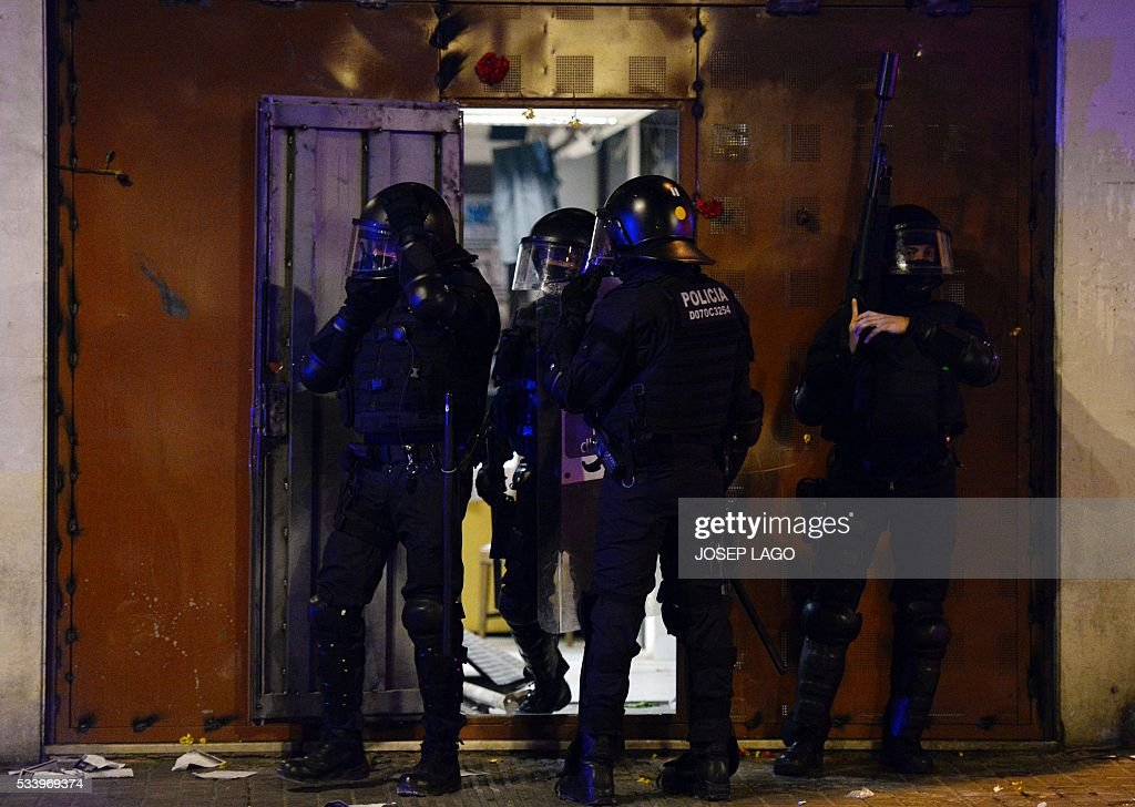 Police officers stand at the entrance of the 'expropiated bank', an occupied old bank branch that was evicted on May 23, 2016, after protesters reopened it during a demonstration in Barcelona on May 24, 2016. LAGO