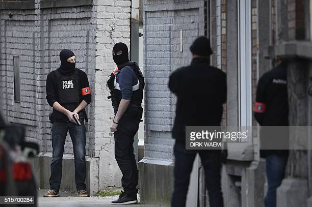 Police officers stand at the site of a shooting on DriesDriesstraat at ForestVorst in Brussels on March 15 2016 Shots were fired on March 15 at...
