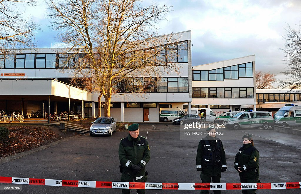 Police officers stand behind a police cordon at the Albertville secondary school in Winnenden southern Germany on March 11 2009 where a teenager in...