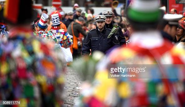 Police officers stand between Carnival revellers during a carnival parade called 'Schull un Veedelszoech' as part of the carnival season on February...