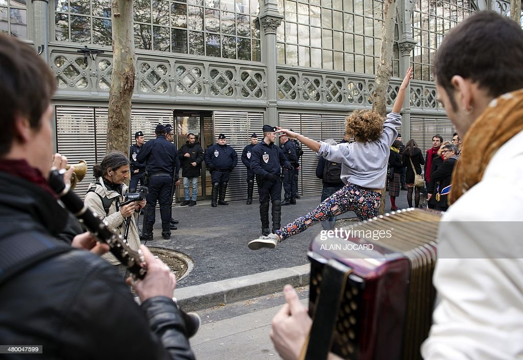 Police officers stand by as artists and technicians working in the entertainment industry play music and dance in front of the Carreau du Temple in Paris on March 22, 2014, as some of their colleagues occupy the building to protest against a planned reform of the rules regulating the unemployment benefits of temporary show business workers (intermittents).