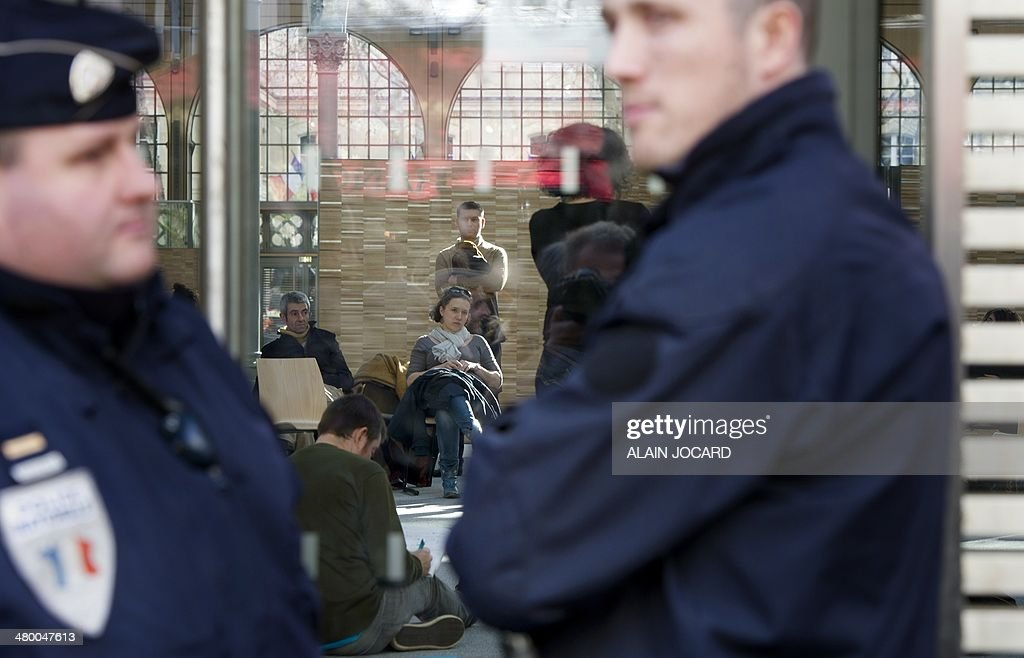Police officers stand by as artists and technicians working in the entertainment industry occupy the Carreau du Temple in Paris on March 22, 2014 to protest against a planned reform of the rules regulating the unemployment benefits of temporary show business workers (intermittents).