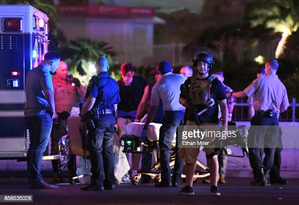 Police officers stand by as medical personnel tend to a person on Tropicana Ave near Las Vegas Boulevard after a mass shooting at a country music...