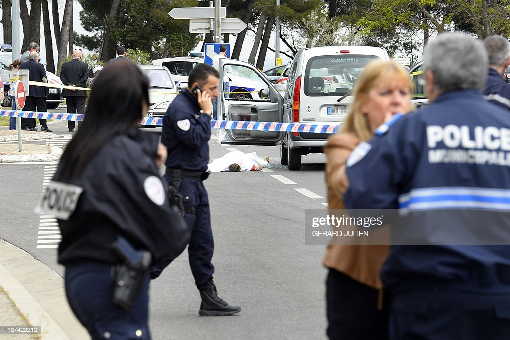 Police officers stand by the site where three persons have been killed and one injured during a shoutout on April 25, 2013 in Istres, near Marseille. A suspect has been arrested.