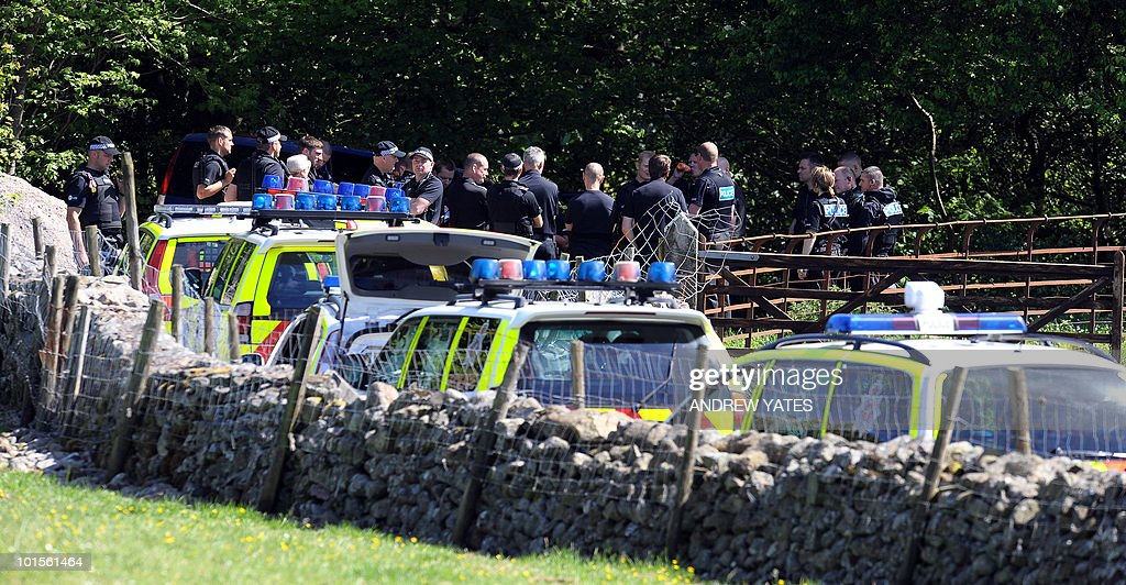 Police officers stand close to where the car belonging to Derrick Bird the suspected gunman was found, and where he is believed to have killed himself, in Boot, near Whitehaven, Cumbria, north west England on June 2, 2010. At least five people were killed when a gunman went on the rampage through one of Britain's most popular tourist regions before apparently killing himself. Derrick Bird, a 52-year-old taxi driver, spent nearly four hours driving through the Lake District in northwest England, reportedly shooting at people in 11 different locations from his car window.