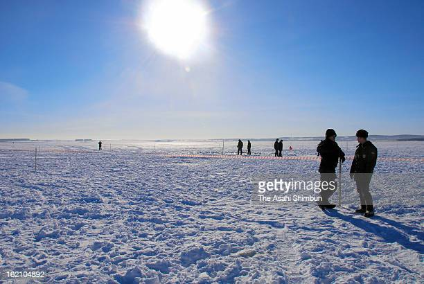 Police officers stand guard a hole in the ice of Chebarkul Lake on March 16 2013 some 80 kilometers from Chelyabinsk Russia Local government reported...