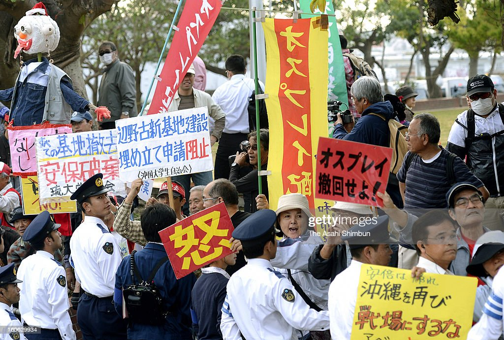 Police officers stand guard against protesters opposing to the MV-22 Osprey deployment on February 2, 2013 in Ginowan, Okinawa, Japan. Japanese Prime Minister Shinzo Abe visits Okinawa for the first time taking office in December.