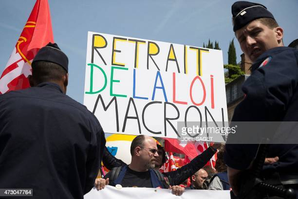 Police officers stand guard as a demonstrator holds a placard reading 'Withdrawal of Macron's law' during a protest organised by several unions...