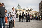 Police officers stand guard as a woman wheels her luggage through Karlsplatz in Munich Germany on Saturday July 23 2016 German Chancellor Angela...