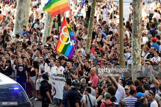 Police officers stand guard as antifarright protesters some of them holding rainbow flags gather against a demonstration by members of the Spanish...