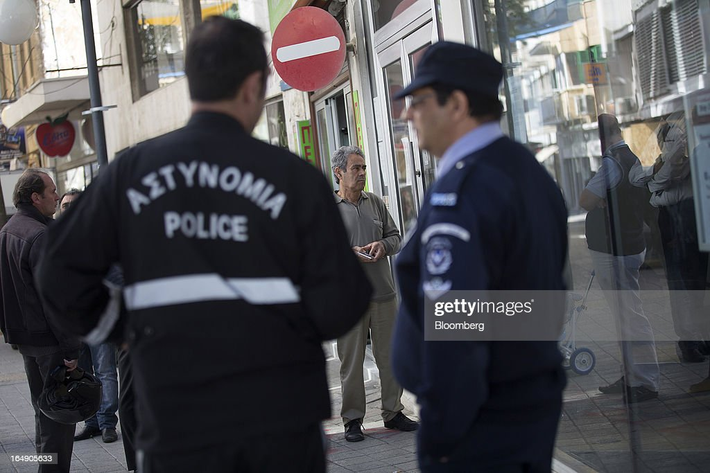 Police officers stand guard as customers wait to be allowed inside a branch of a Cyprus Popular Bank Pcl, also known as Laiki Bank in Nicosia, Cyprus, on Friday, March 29, 2013. Cypriots face a second day of bank controls over their use of the euro as officials in Europe urged the country to move quickly to lift the restrictions, the first time they have been imposed on the common currency. Photographer: Simon Dawson/Bloomberg via Getty Images