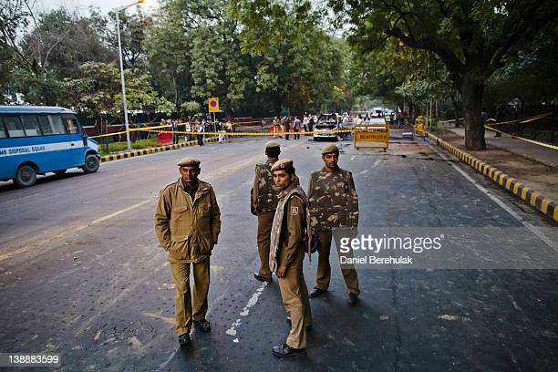 Police officers stand guard as forensics personnel examine a damaged Israeli embassy vehicle after an explosion on February 13 2012 in New Delhi...