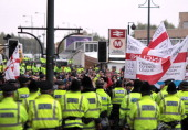 Police officers stand guard as members of the English Defence League demonstrate on Bridge Street in Bradford city centre west Yorkshire on October...
