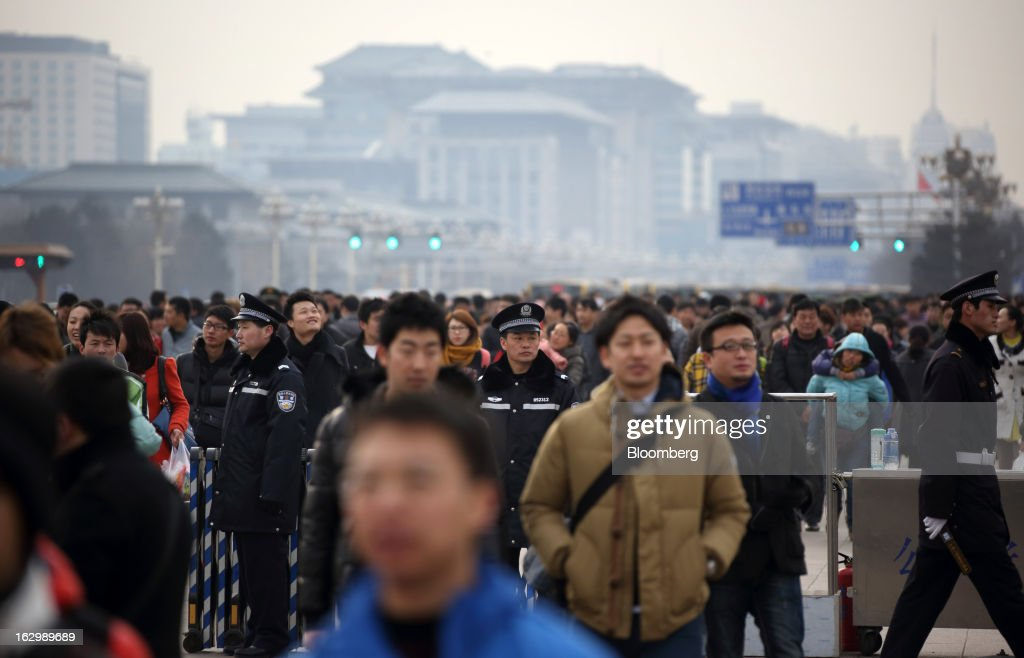 Police officers stand guard as people walk near Tiananmen Gate in Beijing, China, on Saturday, March 2, 2013. Premier Wen Jiabao will this week formally announce this year's economic targets when he delivers his final work report to the National People's Congress, which begins on March 5. Photographer: Tomohiro Ohsumi/Bloomberg via Getty Images