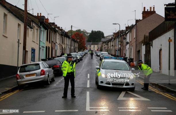 Police officers stand guard at a police cordon near to a house in Newport south Wales on September 20 as they continue their investigations into the...