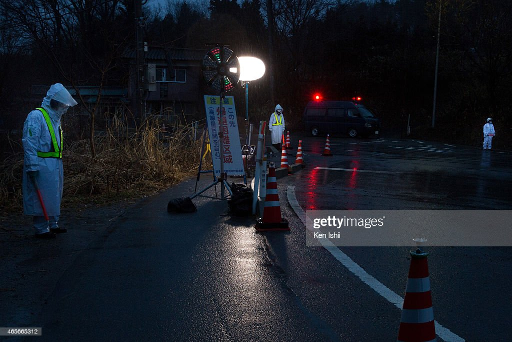 Police officers stand guard at checkpoint to the town within 10km the Fukushima Daiichi Nuclear Power Plant on March 9 2015 in Tomioka town Fukushima...