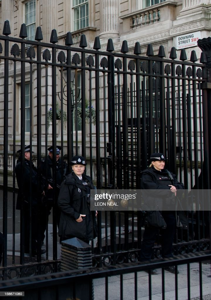 Police officers stand guard at the gates to Downing Street in central London on 23 December, 2012. The British cabinet minister forced to quit over claims he called Downing Street police officers 'plebs' insisted on December 23, 2012 he had been 'stitched up' in his first full account of the furore. Andrew Mitchell said abusive phrases attributed to him were 'hung round my neck in a concerted effort to toxify the Conservative Party and destroy my political career'. AFP PHOTO/Leon Neal