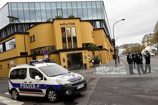 Police officers stand guard behind a cordon erected outside the hotel where the German National football team are staying in Paris on November 13...