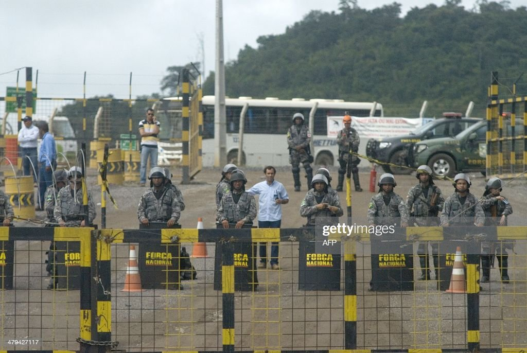 Police officers stand guard during a demonstration against Norte Energia - the company responsible for the construction of Belo Monte hydroelectric power plant - demanding compensation for the loss of income from the flooding of the Xingu river near Altamira, in the northern state of Para, Brazil, on March 18, 2014. The dam will be the largest hydroelectric power plant in Brazil and provide 11% of the nation's electricity. Norte Energia says about 502km2 will be flooded and 117 social, economic and environmental projects are underway for the millions affected in the region.