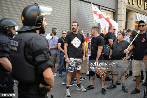 Police officers stand guard during a demonstration by members of the Spanish rightwing group Falange on the Rambla on August 18 a day after a van...