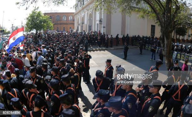 Police officers stand guard during a farmers protest in downtown Asuncion demanding the writing off of their debts on August 9 2017 Farmers are...