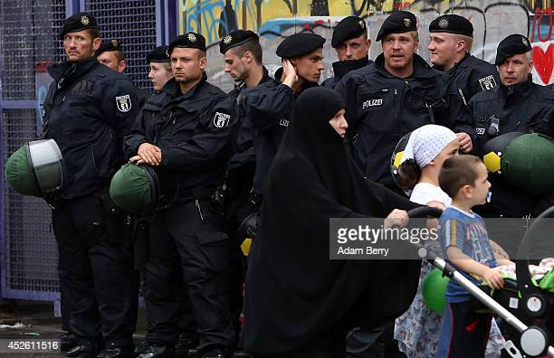 Police officers stand guard during a protest against continued violence in Gaza as a woman in a niqab passes on July 24 2014 in Berlin Germany At...