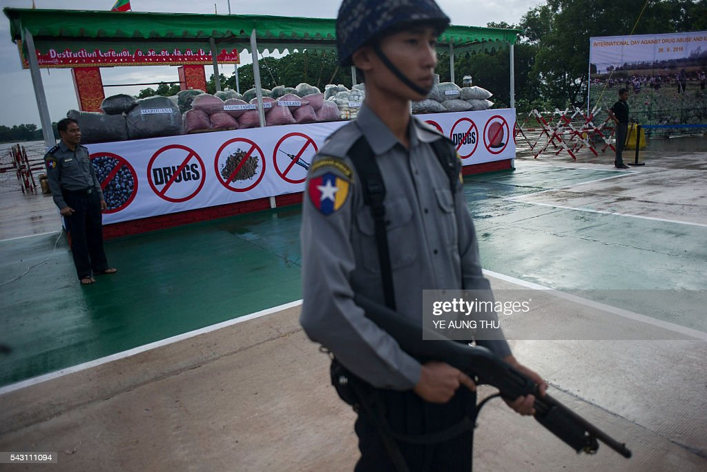 Police officers stand guard in front of seized drugs to be set on fire during a ceremony to mark the UN's 'International Day against Drug Abuse and Illicit Trafficking' in Yangon on June 26, 2016. Myanmar authorities on June 26 destroyed seized narcotics worth 56.31 million USD in anti-drug ceremonies in Yangon, Mandalay and Taunggyi. / AFP / YE