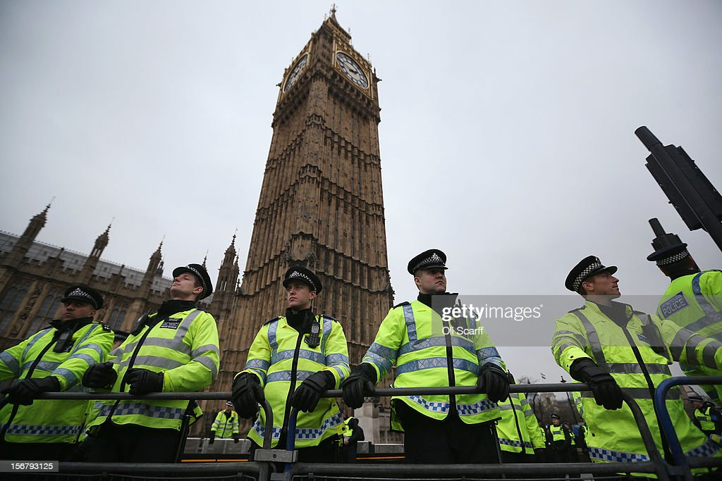 Police officers stand guard in front of the Houses of Parliament as students protest against the rising costs of further education on November 21, 2012 in London, England. The demonstration march was organised by the National Union of Students and is the first national student protest since a series of violent protests against tuition fees two years ago.
